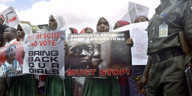A policeman stand beside children calling for the release of missing Chibok school girls at the state government house, in Lagos, Nigeria. Photo / AFP