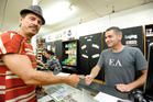 Asher Wallace, 36, purchasing some synthetic cannabis from Tauranga's Specialty T Discount retailer Mike Lawrence on Monday. PHOTO/GEORGE NOVAK