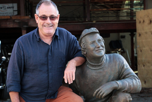 Kevin Harvey with a statue of his late father Les Harvey.