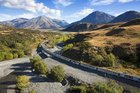The TranzAlpine cruises around a river bend on its Southern Alps traverse of the South Island.