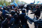 Russian riot police officers scuffle with Crimean tatars at a Russian-Ukrainian border check point outside the town of Armyansk, Crimea. Photo / AP