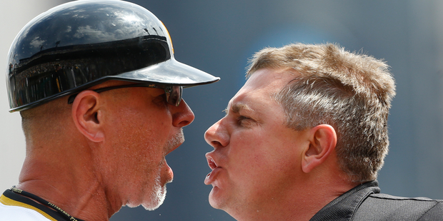 Pirates first base coach Rick Sofield, left, and home plate umpire Greg Gibson practice an acapella version of Bohemian Rhapsody during a break between innings. Photo / AP