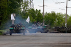 Pro-Russian gunmen atop armored carriers pass by barricades on a road leading into Slovyansk, eastern Ukraine. Photo / AP
