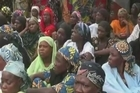 People in Chibok gather outside the school where hundreds of girls were abducted by Islamist militant group Boko Haram.