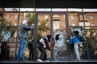 Pro-Russian activists break the glass of the offices of Industrial Union of Donbass Corporation in Donetsk. Photo / AP