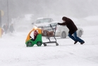 A woman pushes her daughter and groceries in Saginaw Michigan.