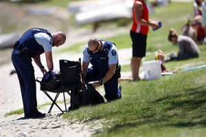 Police gather up possessions belonging to a snorkeller who nearly drowned at Pilot Bay yesterday. Photo/George Novak