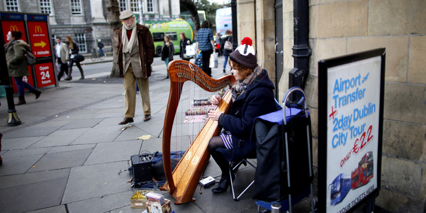 A woman plays the harp in Dublin city centre, Ireland. On Sunday, Ireland officially ends its reliance on a 67.5 billion-euro loan program.