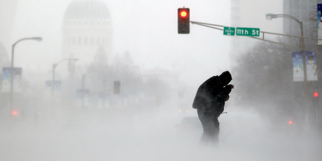 A person struggles to cross a street in blowing and falling snow in St. Louis. Photo / AP