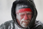 Allan Umscheid, owner of Yards By Al in Lawrence, Kan, feels the bitter wind as he runs a snow blower early Sunday morning. Photo / AP