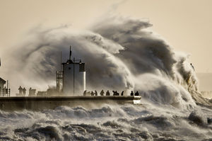 People watch and photograph enormous waves as they break, on Porthcawl harbour, South Wales. Photo / AP