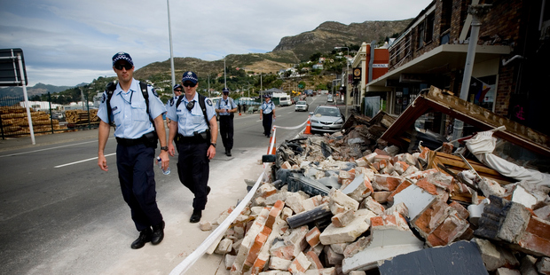 Australian police walk past some of the destruction in Lyttelton a week after the 6.3-magnitude earthquake hit Christchurch in 2011. Photo / Dean Purcell