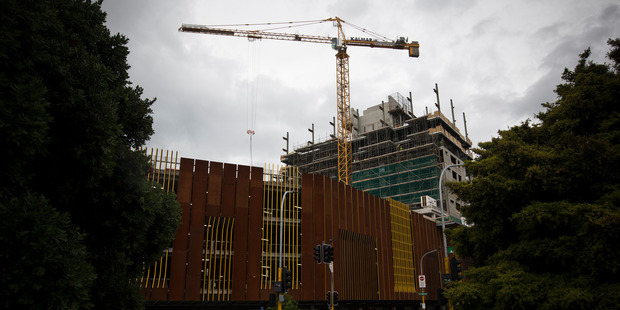 A crane moves construction materials onto the 10-storey apartment tower in the Merchant Quarter, on McCrae Way, New Lynn. Photo / APN