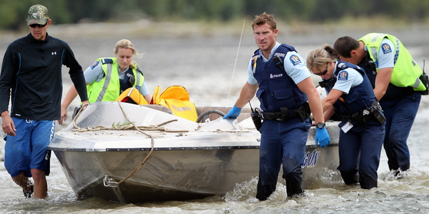Police move the jetboat down river. Photo/Paul Taylor