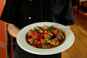 Silk Road Uyghur Cuisine chef Rizaydn Reyim with his dish, spicy lamb feet. Photo / Brett Phibbs