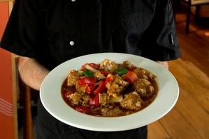 Silk Road Uyghur Cuisine chef Rizaydn Reyim with his dish, spicy lamb feet. Photo / Brett Phibbs