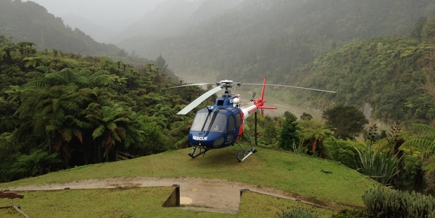 The rescue helicopter lands on the lawn of the Bridge to Nowhere Lodge to pick up an injured man. Photo/Supplied