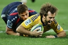 Skipper Conrad Smith scores despite Tom English's best tackling efforts in the Hurricanes-Rebels match in Melbourne on Friday night.  Photo / Getty Images