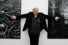 Hans Ruedi Giger, seen here posing with his art in 2007, has died at the age of 74. Photo/AP