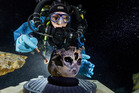 Diver Susan Bird, working at the bottom of Hoyo Negro, a large dome-shaped underwater cave in Mexico's Yucatan Peninsula, brushes a human skull. Photo / AP