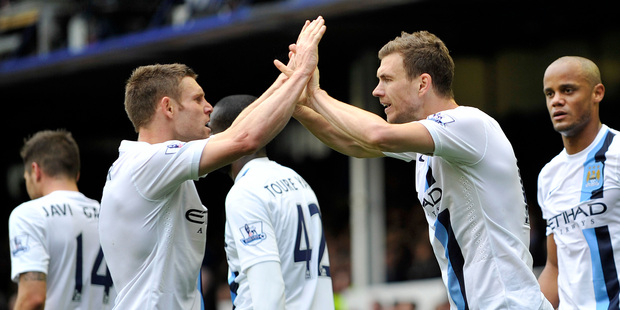 Manchester City's Edin Dzeko, right, celebrates with teammate James Milner after scoring the second goal of the game during their English Premier League soccer match against Everton. Photo / AP