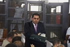 Farag Fathi, lawyer for Al-Jazeera's Australian correspondent Peter Greste (background in cage) prepares to leave the court as he decided to quit the case. Photo / AFP