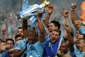 Manchester City's players captain Vincent Kompany, center, holds the Cup and celebrates with teammates after being crowned Premier League Champions, something many fans missed. Photo / AP