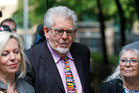Veteran Australian entertainer Rolf Harris, centre, who is accused of indecent assault, accompanied by members of his family as he arrives at court. Photo / AP