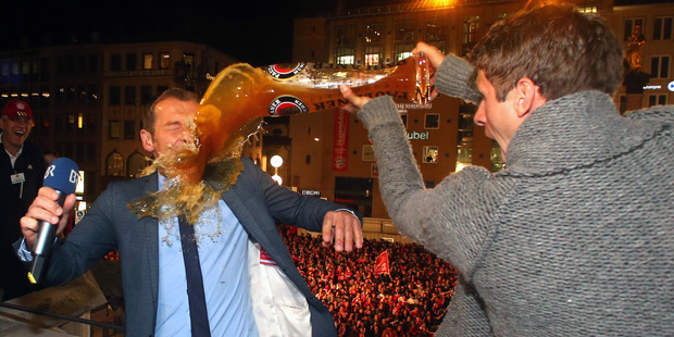 German TV presenter Markus Othmer, is sprayed with beer by Bayern Munich player Thomas Mueller. Photo / AP