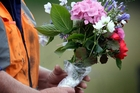 GIFT: Flowers from a passerby arrive as emergency crews work at the fatal crash.PHOTO/FILE