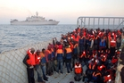 Illegal migrants rescued in the Mediterranean by the Italian coastguard wait to board a navy ship. Photo / AP