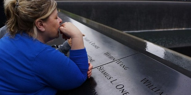 A woman pauses at the names engraved along the pool at the Ground Zero memorial site. Photo / AFP
