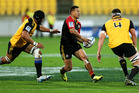 Tim Nanai-Williams of the Chiefs looks to offload under pressure from Victor Vito (L) and Jeremy Thrush of the Hurricane. Photo / Getty.