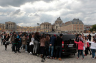 Fans look inside one of the cars for Kim Kardashian, Kanye West and their guests, at the entrance of the Chateau de Versailles in Versailles, France. Photo / AP
