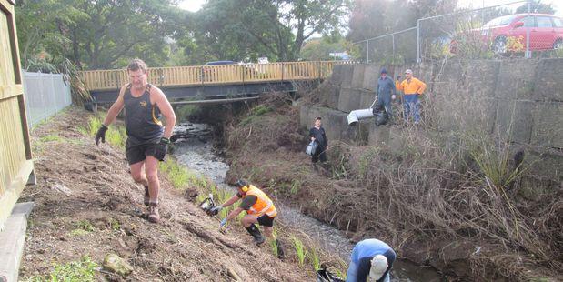 Habitat Enhancement and Landcare Partnership (Waihi) members clean up and plant Mangatoetoe stream bed near the town bridge.