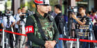 An armed Thai military police stands guard at the entrance to a hall of the army club prior to a meeting between Thai Armed Forces Chiefs and high ranking officials. Photo / AP