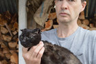 John Bennett, with his sister's cat Midnight, which someone stole and set alight last week. Photo / Greymouth Star