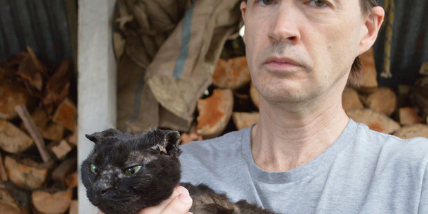 John Bennett, with his sister's cat Midnight, which someone stole and set alight. Photo / Greymouth Star