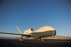 An RQ-4 Global Hawk unmanned aerial vehicle sits on a flight line.