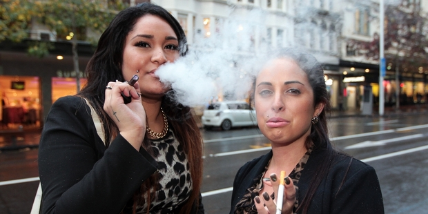 Angela Teu, left, puffs on an e-cigarette in Queen St, Auckland, yesterday, while Shevon Halloran sticks with the standard tobacco type. Photo / Doug Sherring