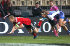 Johnny McNicholl of the Crusaders scores a try in the tackle of Nick Cummins. Photo / Getty Images
