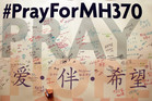 A man writes messages for passengers aboard the missing Malaysia Airlines Flight MH370. Photo / AP