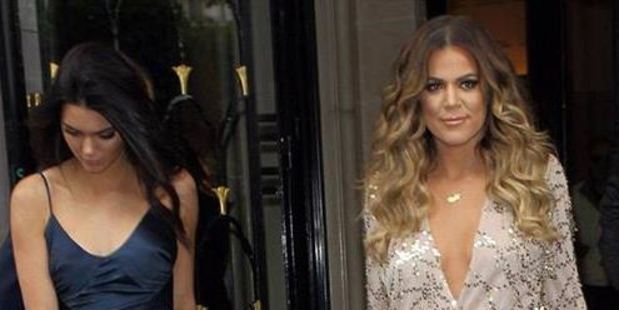 Kendall Jenner (left), with Khloe Kardashian, shows off her Johanna Johnson design in Paris.