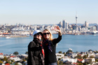 Alison Lawrence (left) and Molly Lawrence-Webb from New Hampshire enjoy the glorious winter sun at the top of Mt Victoria in Devonport. Photo / Chris Gorman