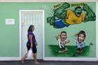A mural depicting Brazilian soccer player Hulk flying over Argentina's Lionel Messi, and Portugal's Cristiano Ronaldo in Rio. Goldman Sachs tips Brazil to win the World Cup. Photo / AP