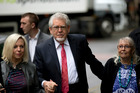 Australian born veteran TV and music entertainer Rolf Harris, center, arrives for his trial with his wife Alwen Hughes, right, and daughter Bindi. Photo / AP