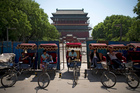 Chinese trishaw drivers wait for customers at a compound being fenced up for refurnishing near the drum tower. Photo / AP