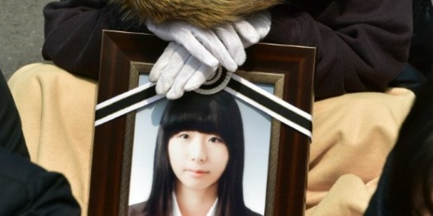 A family member holds a portrait of a teen who died in the Sewol ferry disaster. Photo / AFP