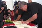 Rangitane Marsden adds his signature to Ngai Takoto's deed of settlement. Photo/Peter de Graaf