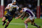 Johnathan Thurston fends off Will Chambers during the Cowboys' 22-0 victory over the Storm. Photo / Getty Images.